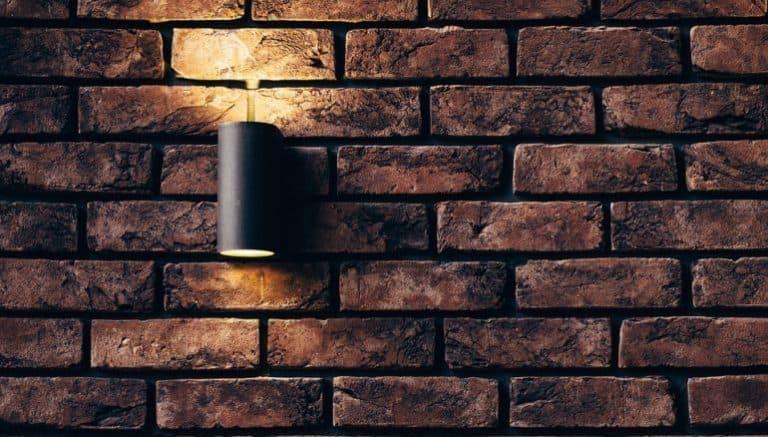 Ein schwarzer Bewegunsmelder vor einer Backsteinwand