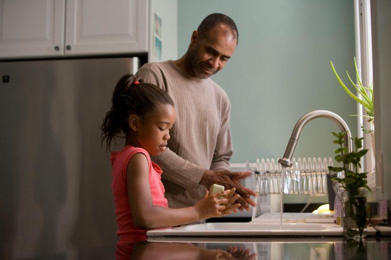 Vater und Tochter beim Abspülen, Wasserhahn läuft